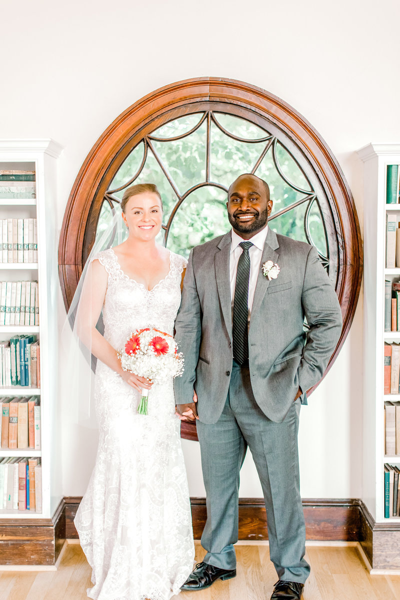 Bride and groom smile holding hands at Old Town Hall in Fairfax, Virginia