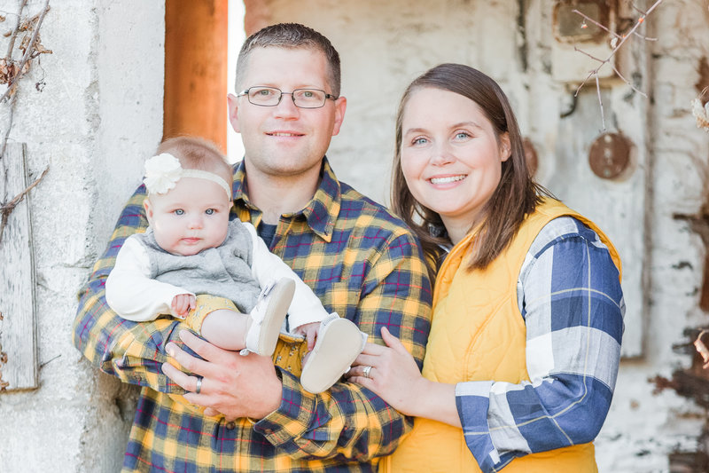Mother and father hold baby girl during family photo session outdoors