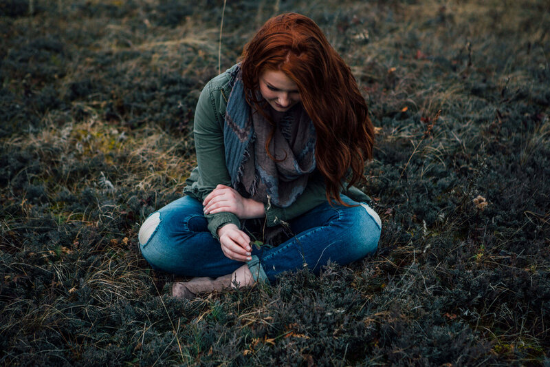 girl with red hair cross legged in grass