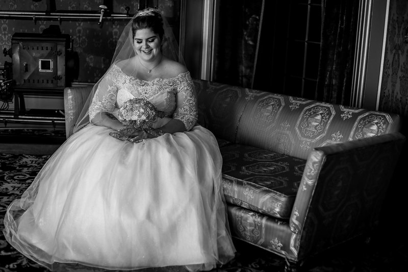 Bride sitting on a sofa in the lobby of the Warner Thetare