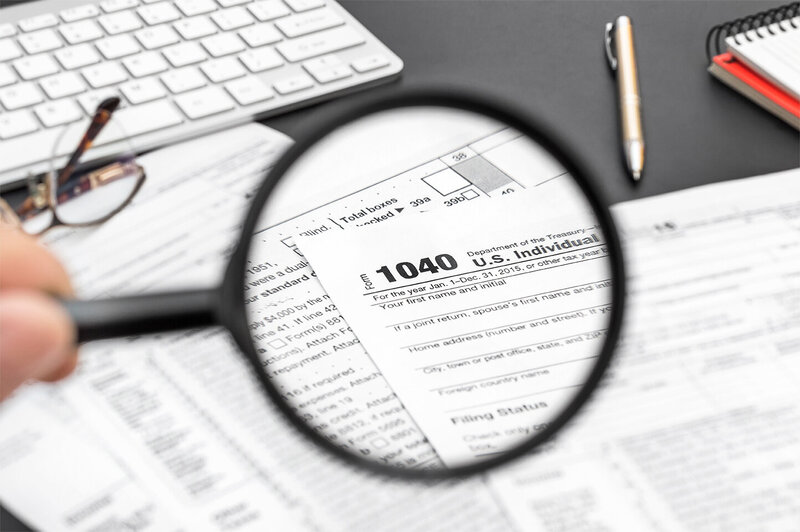 individual tax form 1040 viewed on desk with magnifying glass