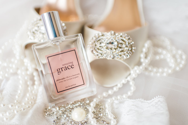 Amazing Grace perfume resting against white bridal shoes and pearls draped in the background.
