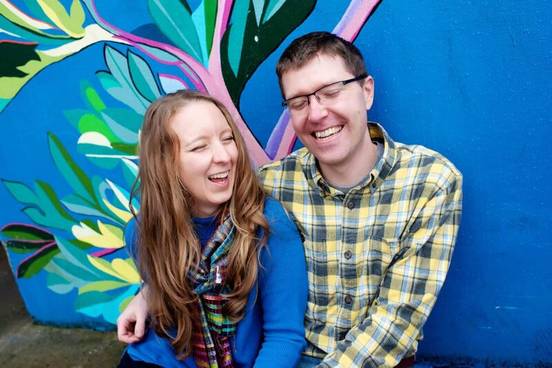 a man and woman sit and laugh with closed eyes in front of a colorful painted mural wall