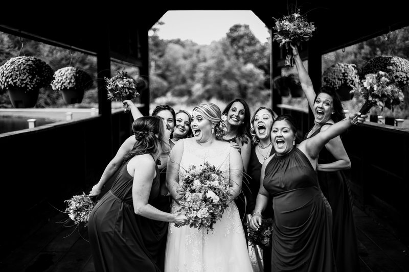 Bride and her birdesmaids on covered bridge at Majestic Woods