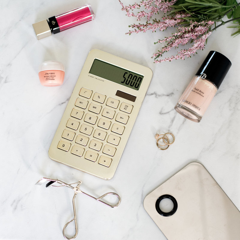 View of marble countertop with various makeup products and a calculator