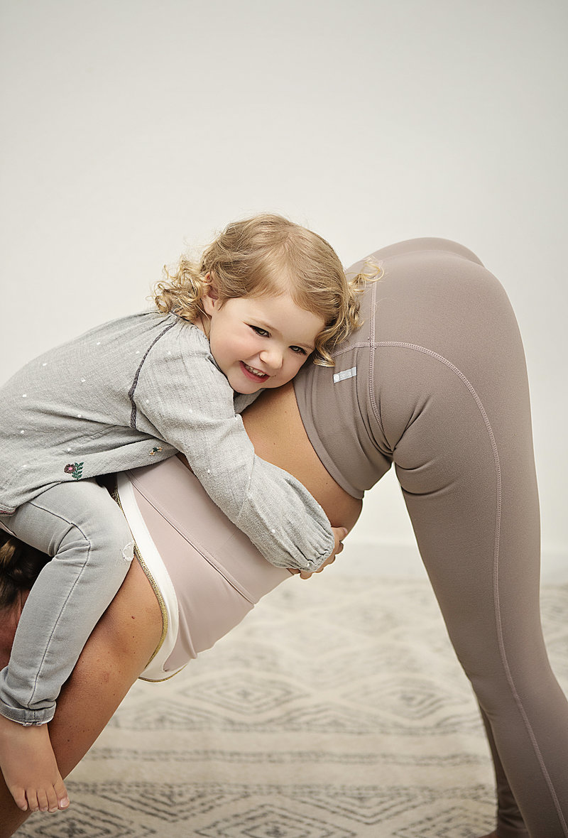 Toddler girl hugs her mom's back while her mom holds a downward dog yoga pose at Hotsource Yoga in Aptos