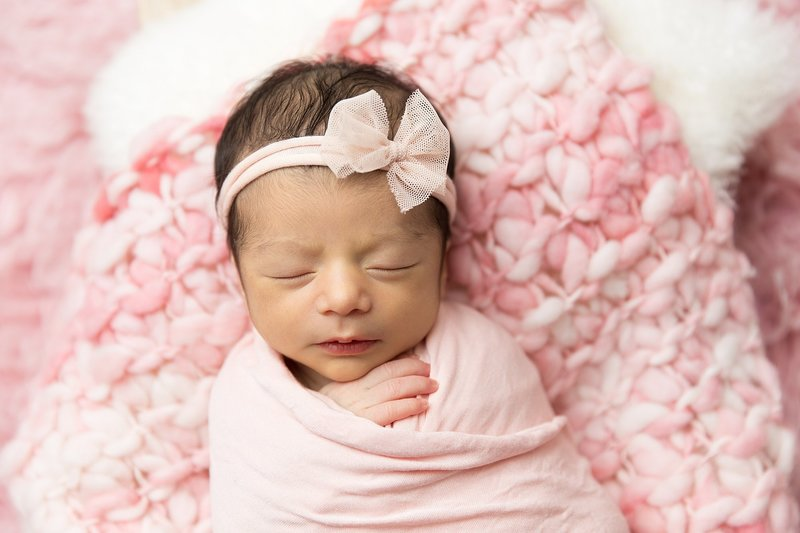 baby girl with pink bow little hand peeking out