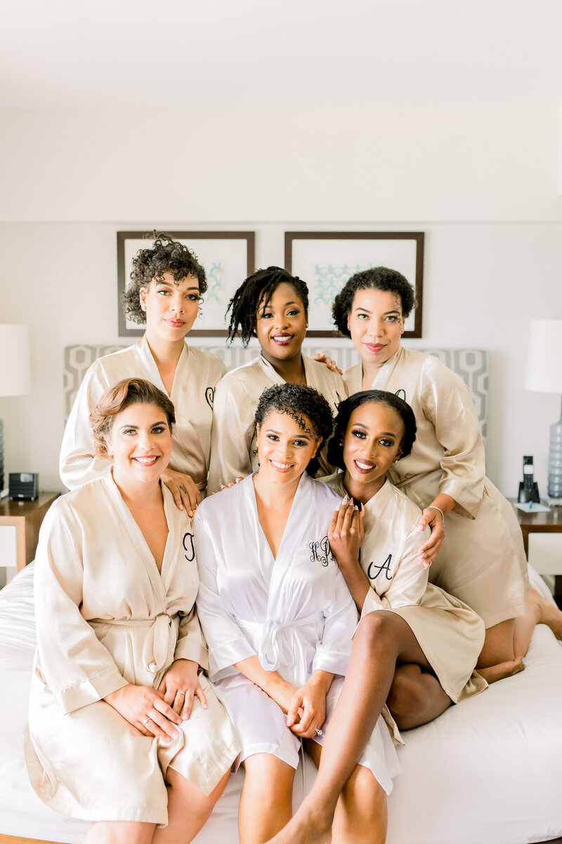 bride and bridesmaids in gold silk robes on bed