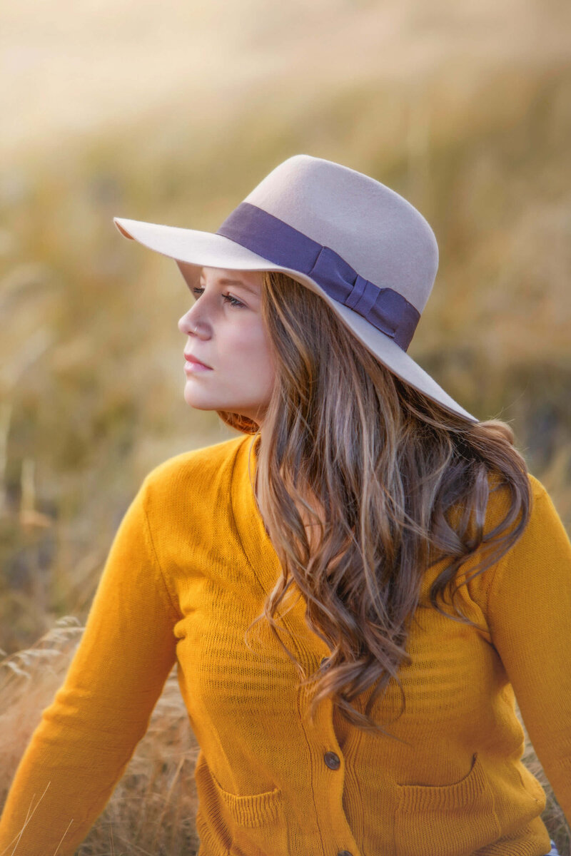 model with hat in field of grass