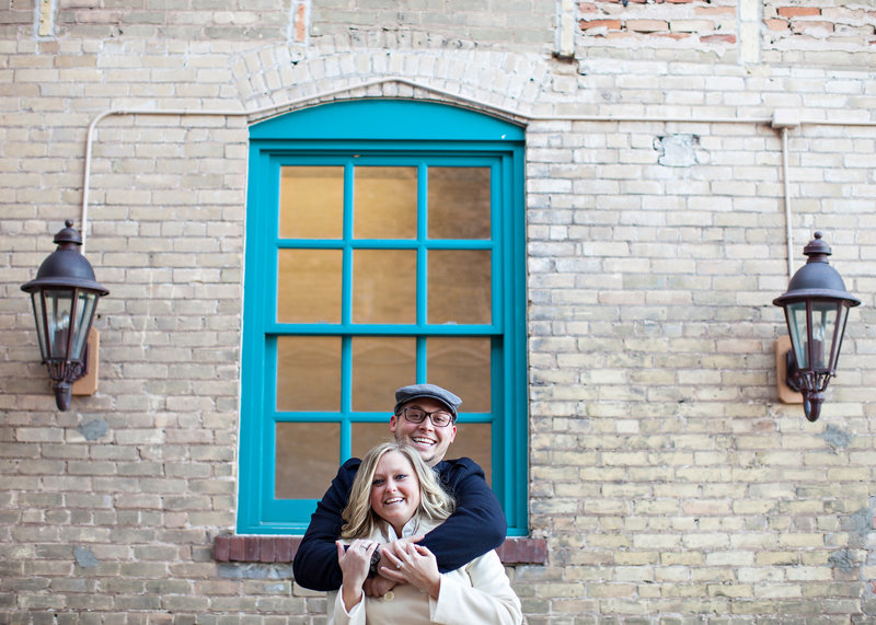 Engaged couple hugging in front of blue window and brick wall.