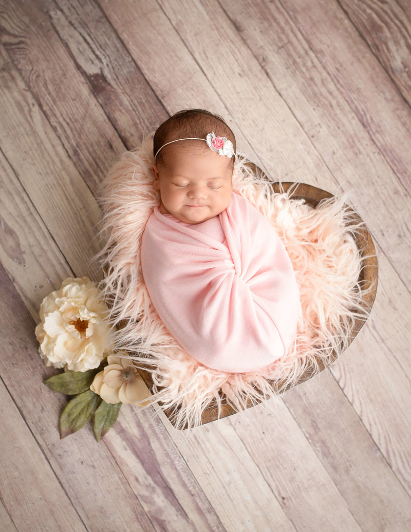 Sweet newborn girl posed at our Rochester, Ny studio.