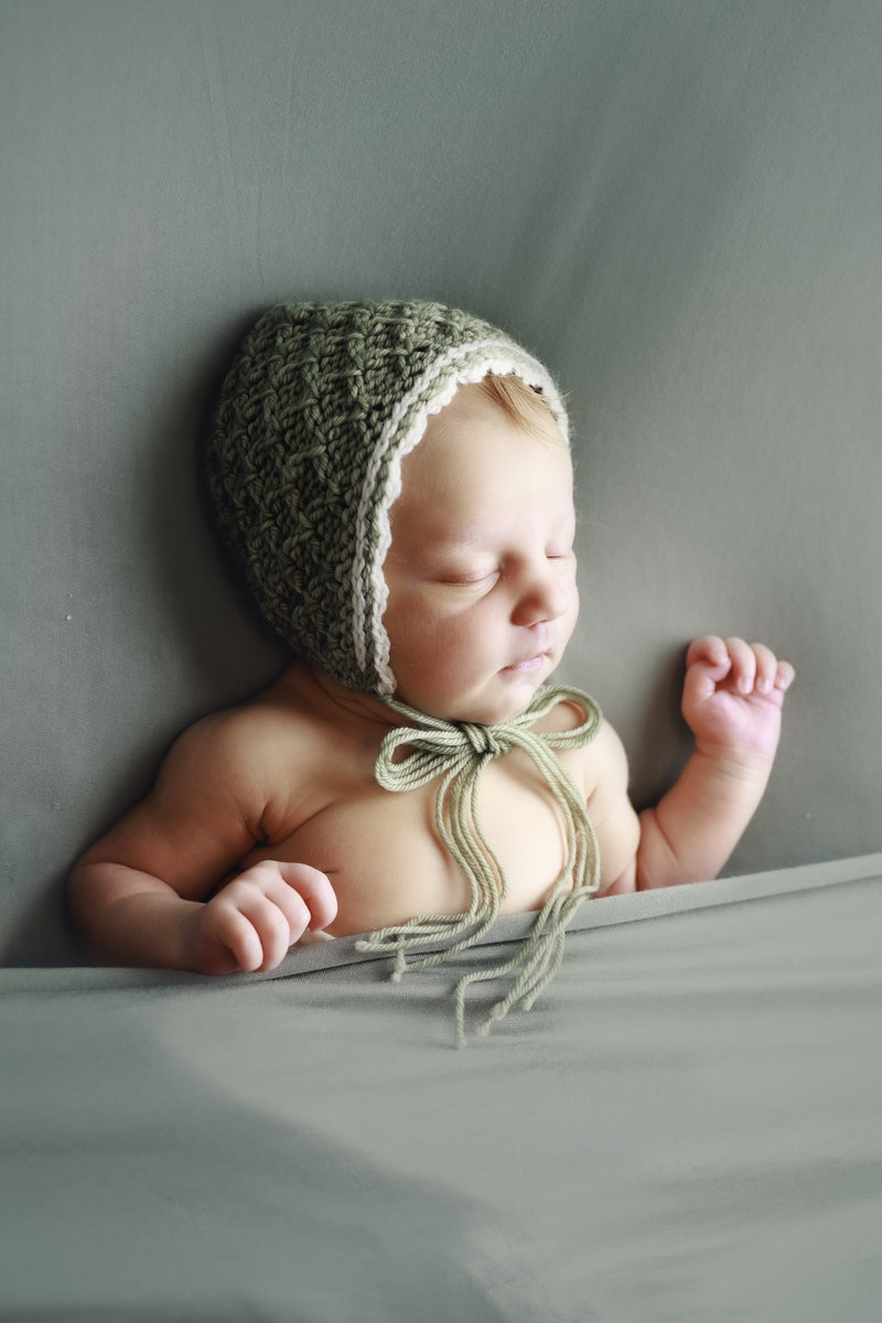 Newborn baby girl with knitted bonnet laying on her back on a blue backdrop