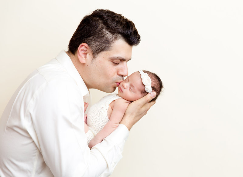 Dad with newborn baby girl kiss on the cheek