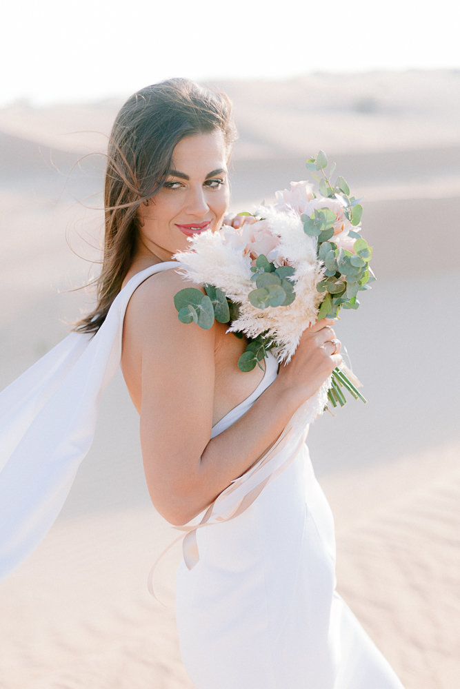 woman holding a bouquet of flower for her wedding in the desert
