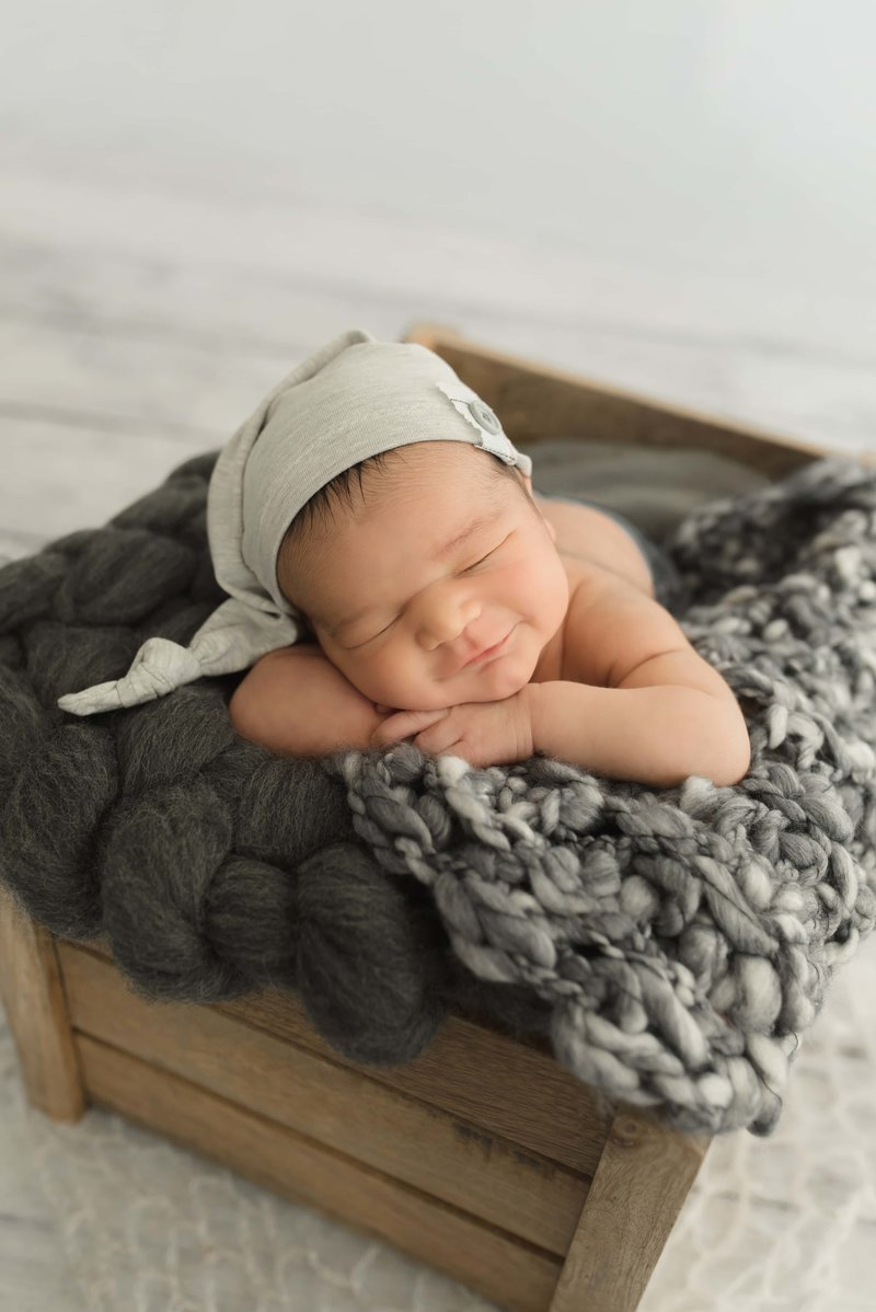 sleeping newborn smiles posed with his chin on his hands and lying on fluffy blankets