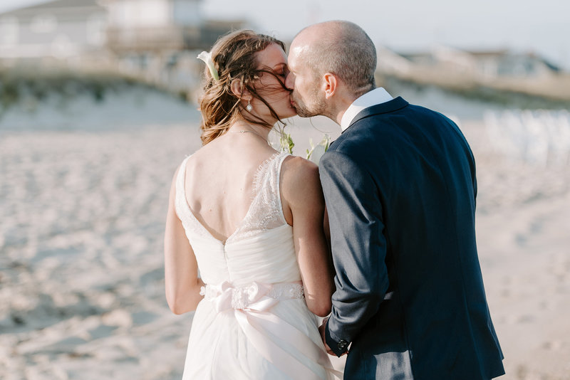 bride and groom share sweet kiss after beach wedding