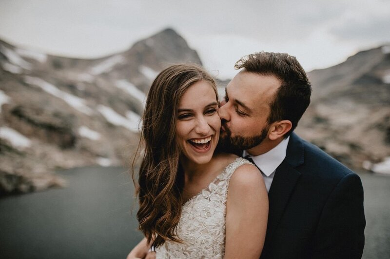 Wedding couple kiss on the cheek for mountain hiking elopement photoshoot
