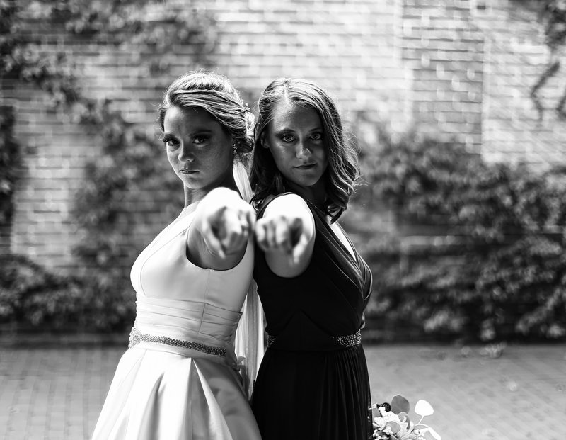 Bride and maid of honor stand back to back and point at the camera in Modern Tool Square in Erie, PA
