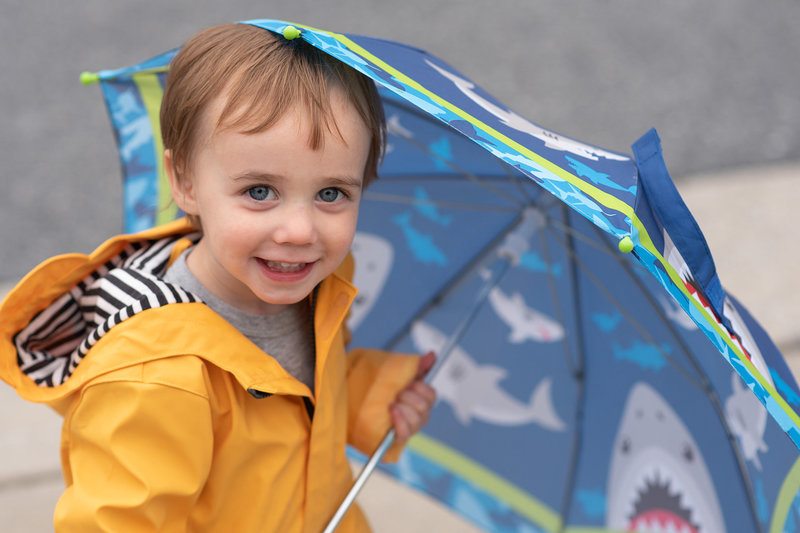 Little boy peeking out from under blue umbrella