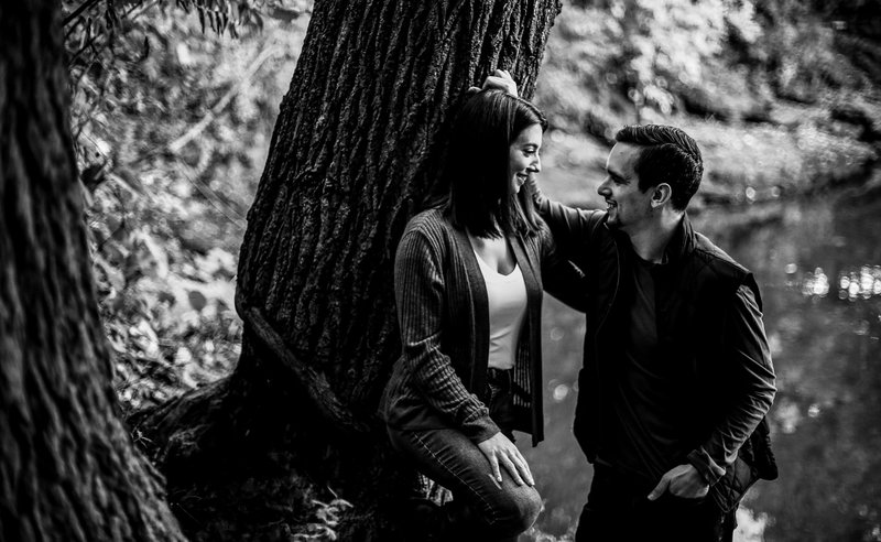 Couple leaning against  big tree during engagement photos at Frontier Park