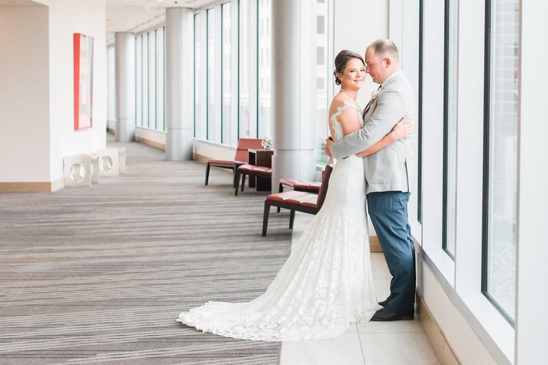 Bride and groom hug in hallway of sophisticated Denver Art Hotel.