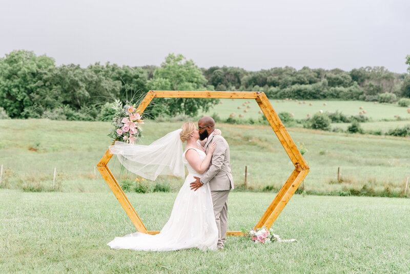 A bride and groom kiss in front of their wedding arbor with the Rose Oak acres farmland behind them.