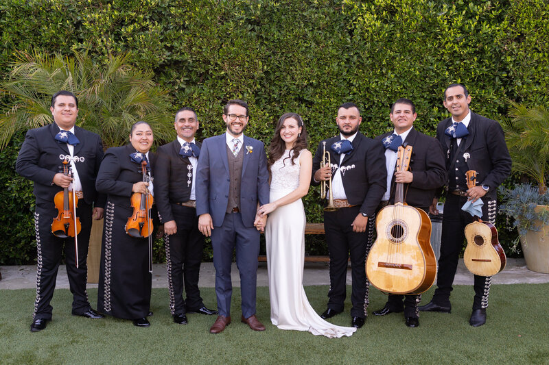 Bride and groom surrounded by mariachi band at their wedding reception