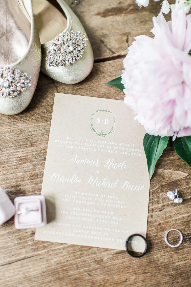 Wedding invitation displayed with the rings, bouquet and bridal shoes.
