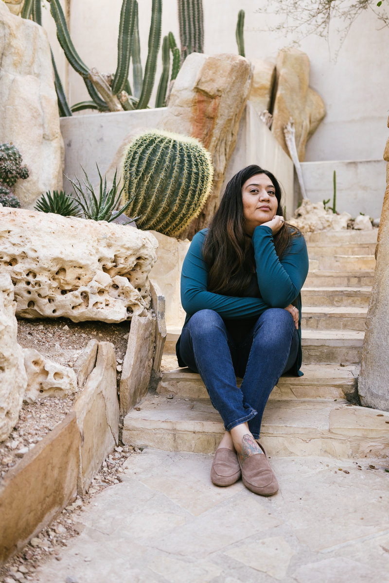 San Antonio Photographer Irene Castillo sitting on stairs surrounded by succulents and cactus