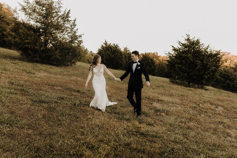 Bride and groom holding hands and walking in a field