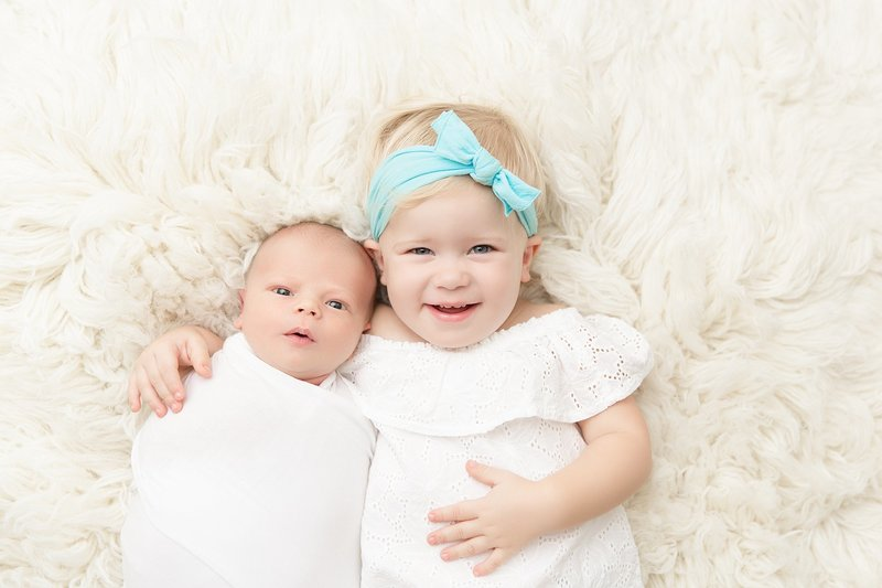 Baby sister with new baby brother wearing white