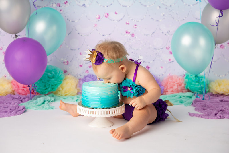 birthday girl eats cake in front of a mermaid themed studio set