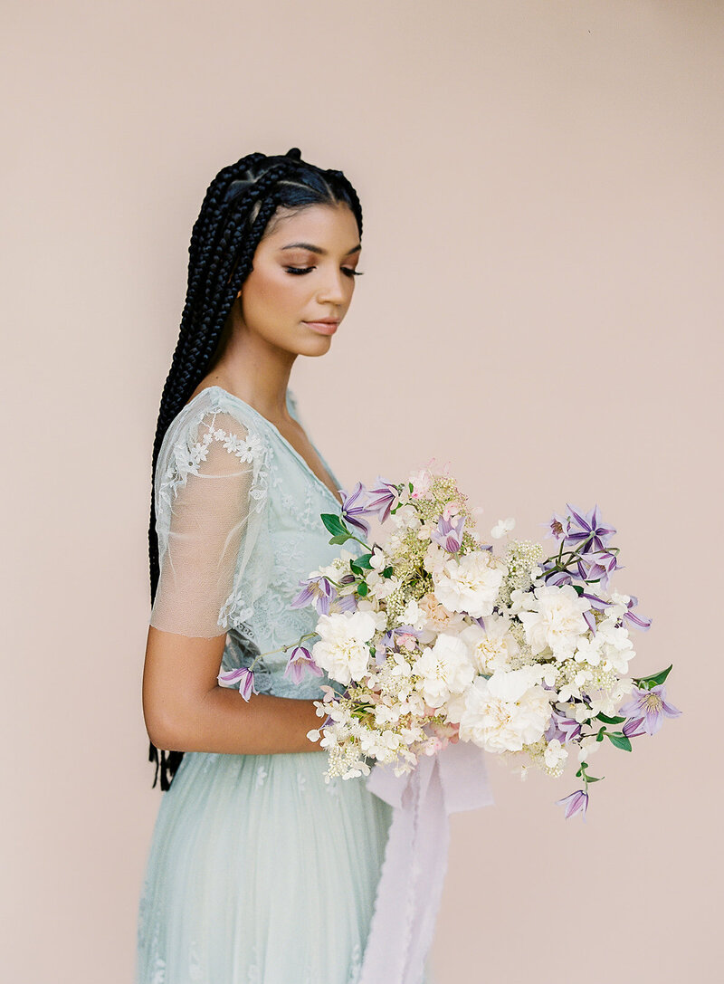 black-bridesmaid-with-braids-in-a-light-green-dress-with-bouquet