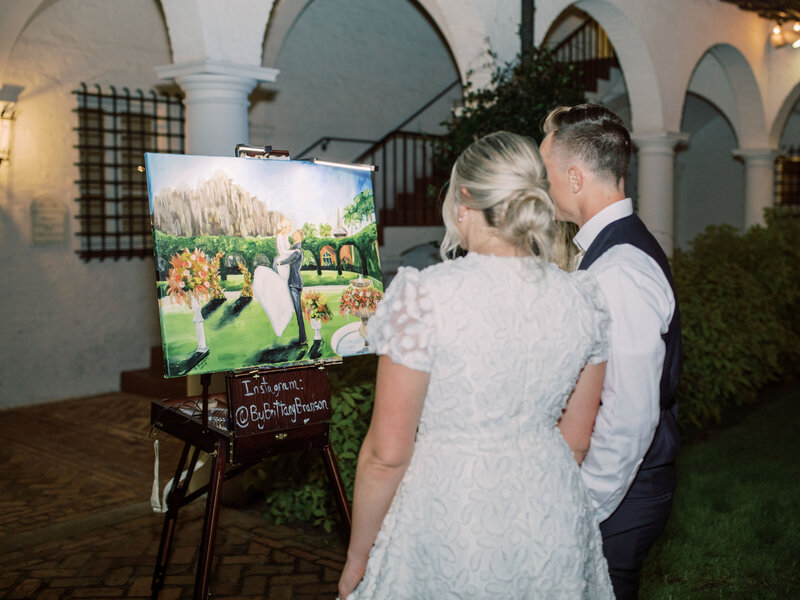 Bride and groom admiring a live wedding painting at the Crane Cottage at Jekyll Island Club