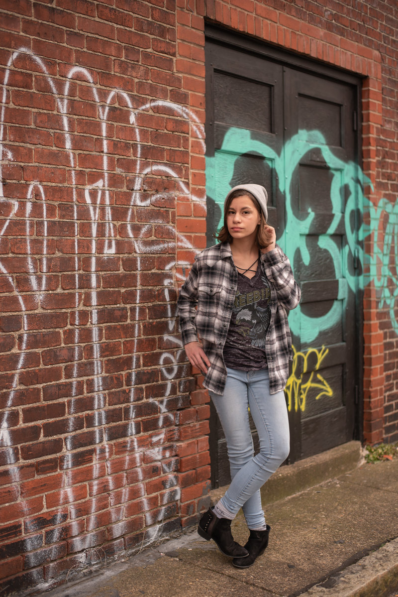 Teenage girl in flannel and knit hat leaning against graffitied brick wall