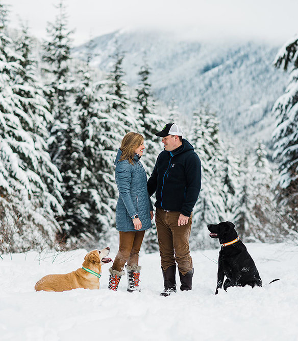 a couple takes their dogs for a walk during their adventurous engagement session at crystal mountain with mountain elopement photographer amy galbraith