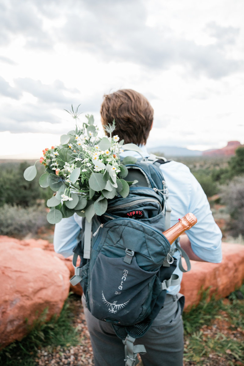 an adventurous hiking groom wears a backpack full of his bride's bouquet and a bottle of champagne.