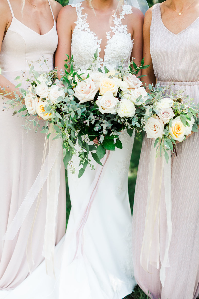 Bridesmaids in dresses holding wedding bouquets
