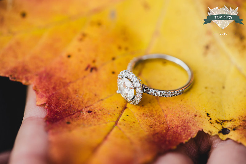 Engagement ring pictured on a golden orange fall leaf