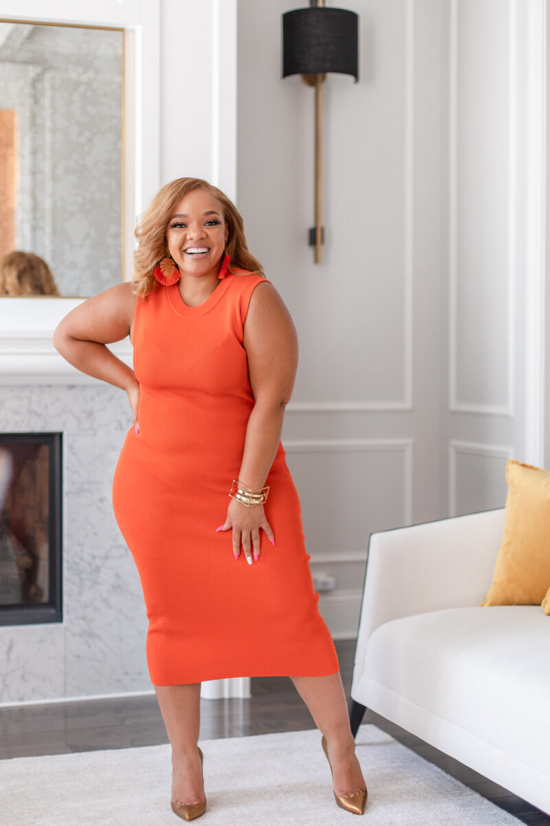 Digital Marketing coach smiling with hand on her hip in bright orange dress