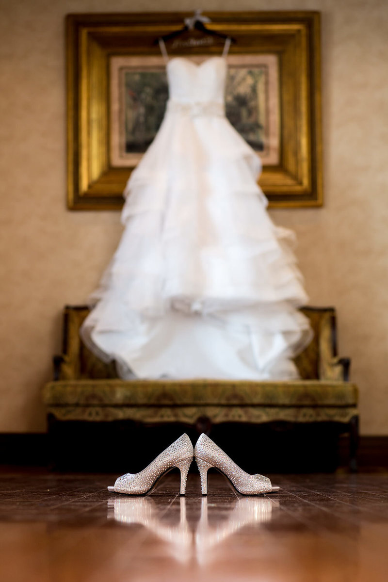 Wedding shoes with gown hanging in the background