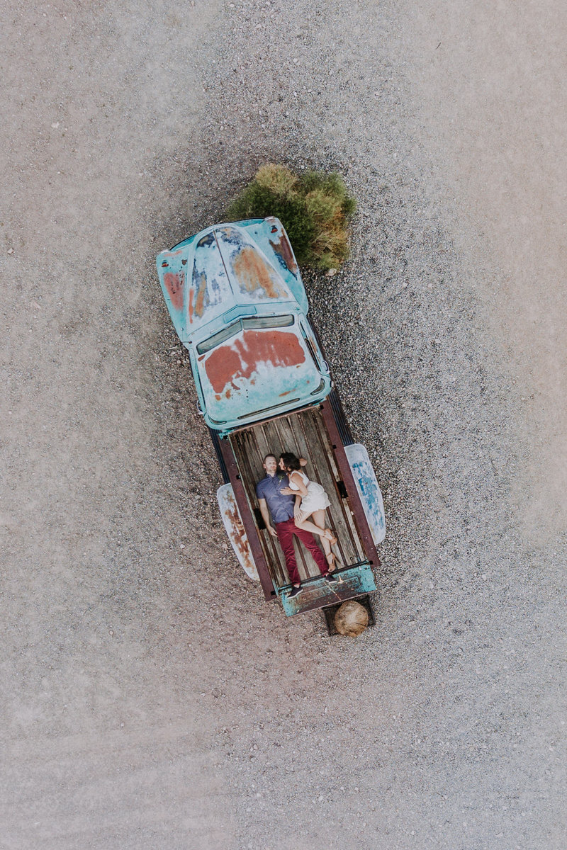 Lake Tahoe wedding pictures a bride in groom lay in the bed of a truck in the desert
