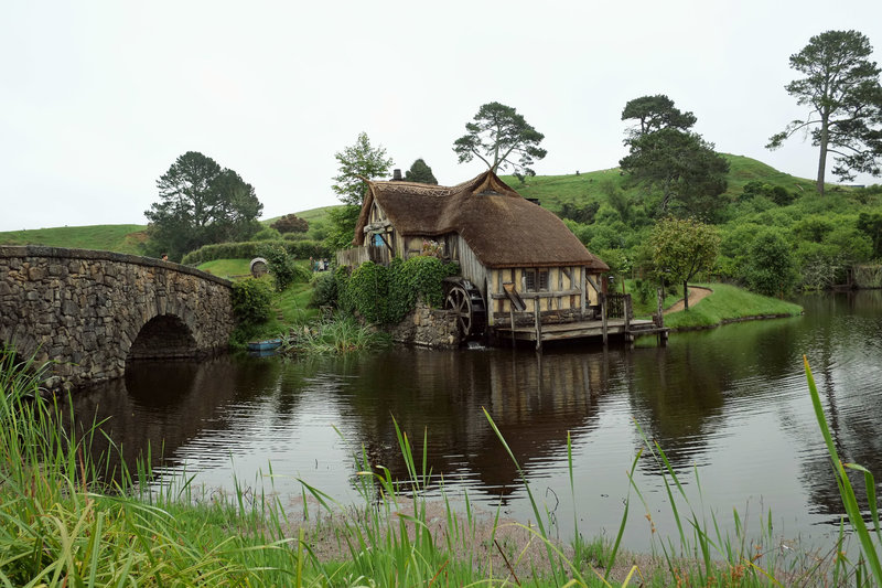 A photo from Hobbiton in New Zealand of a house on a small lake