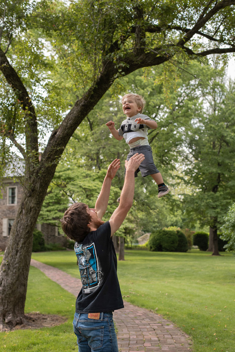 Daddy throwing little boy into air