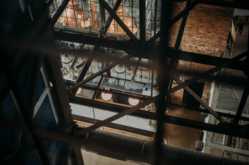 metal framing blurred out i the foreground looks down on a bar with spherical lights and brick wallsa view down to the tasting room of philadelphia distilling company shot by philadelphia wedding photographer alex medvick