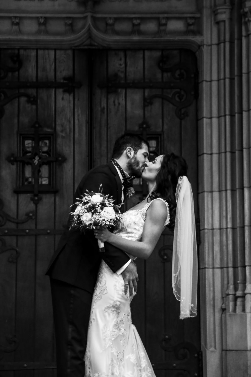 Bride and groom kissing outside the doors to the First Presbyterian Church of the Covenant in Erie, PA