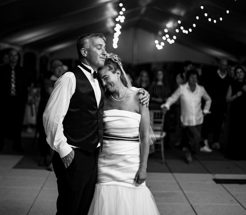 Bride leans on groom's shoulder on the dance floor at their Anchor Plaza wedding reception in Erie PA