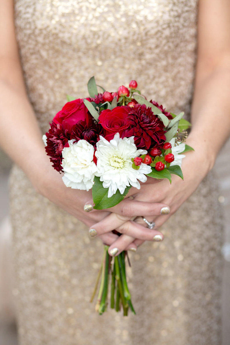 red and white bridesmaid bouquet against a gold sequin gown