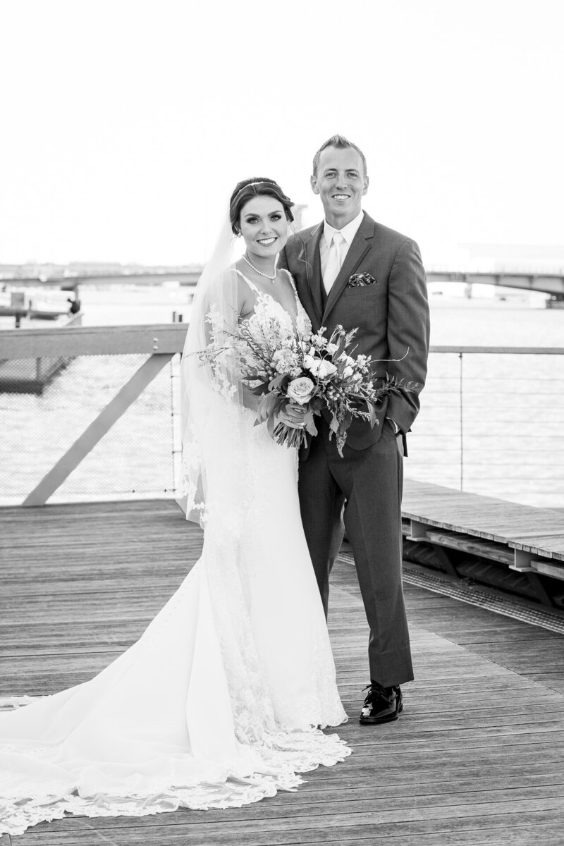 bride and groom see each other for the first time wedding day first look on pier near detroit river and bridge