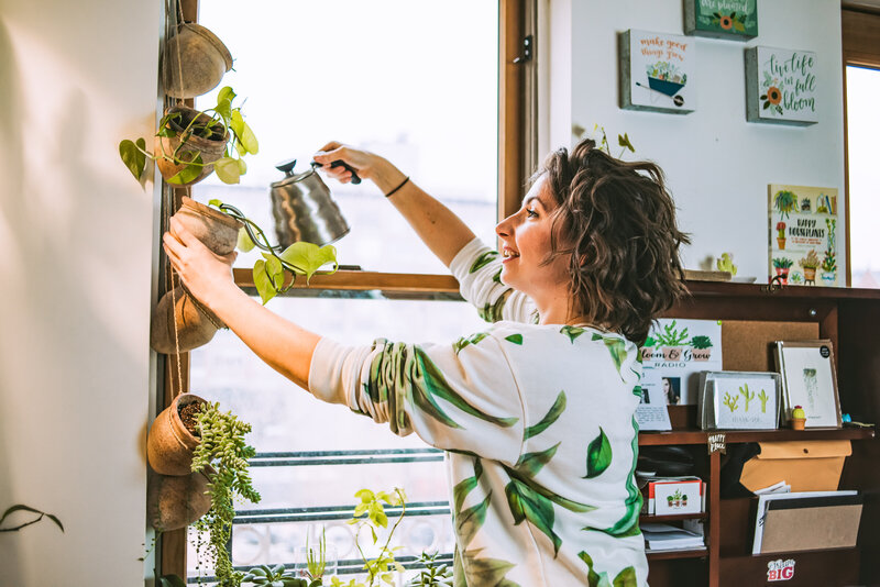 Woman waters her hanging plants in her apartment window
